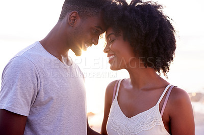 Buy stock photo Cropped shot of a young attractive couple being affectionate while spending time together on the promenade at the beach