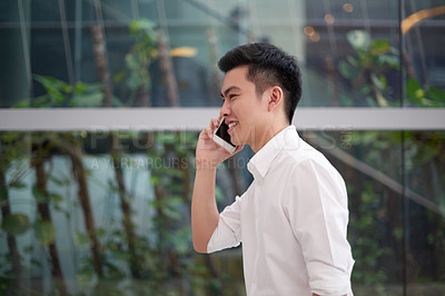Buy stock photo Shot of a confident young man walking to work while talking on his cellphone inside of a building during the day