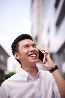 Buy stock photo Shot of a cheerful young man walking in the busy streets of the city while talking on his cellphone outside during the day