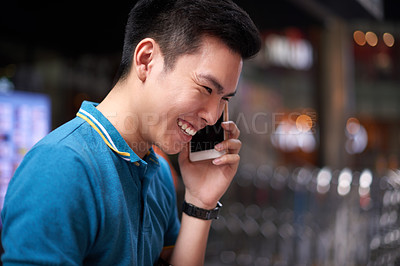 Buy stock photo Shot of a cheerful young man talking on his cellphone while standing in the busy streets of the city during the day