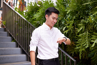 Buy stock photo Shot of a confident young businessman walking down a staircase while looking at the time on his wristwatch outside during the day