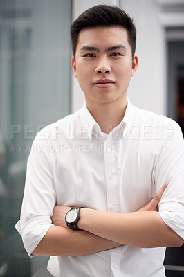 Buy stock photo Portrait of a confident young businessman standing in the office at work while looking directly at the camera during the day