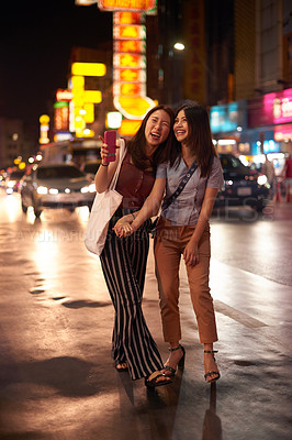 Buy stock photo Shot of two happy young friends enjoying a night out in the city