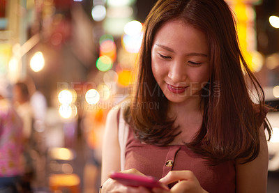 Buy stock photo Shot of a young woman using a mobile phone on a night out in the city