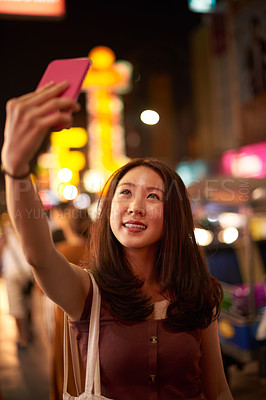 Buy stock photo Shot of a happy young woman taking a selfie with a mobile phone on a night out in the city