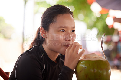 Buy stock photo Cropped shot of an attractive young woman enjoying a beverage at a beachside cafe