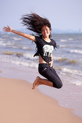 Buy stock photo Full length portrait of an attractive young woman jumping joyfully on the beach