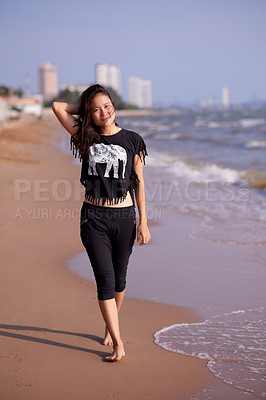 Buy stock photo Full length portrait of an attractive young woman walking along the beach