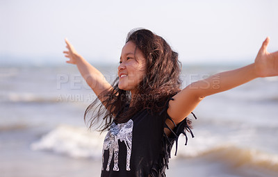 Buy stock photo Cropped shot of an attractive young woman standing with her arms outstretched at the beach