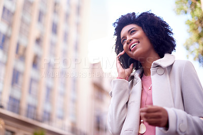 Buy stock photo Low angle shot of an attractive and fashionable young woman making a phonecall while walking in the city