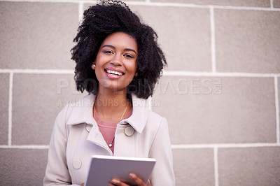 Buy stock photo Cropped portrait of an attractive and fashionable young woman using her tablet while walking in the city
