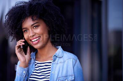 Buy stock photo Shot of a young designer talking on a cellphone outside an office