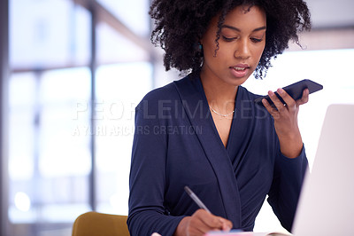 Buy stock photo Shot of a young businesswoman talking on a cellphone while writing notes in an office