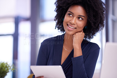 Buy stock photo Shot of a young businesswoman looking thoughtful while using a digital tablet in an office