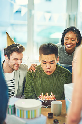 Buy stock photo Cropped shot of a handsome young man blowing out birthday candles while surrounded by friends at his party