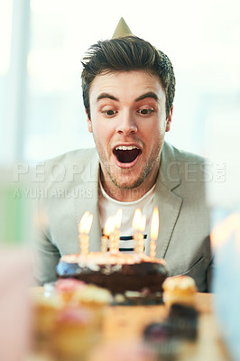 Buy stock photo Cropped shot of a handsome young man blowing out his birthday candles