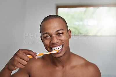 Buy stock photo Portrait of a handsome young man brushing his teeth in the bathroom at home