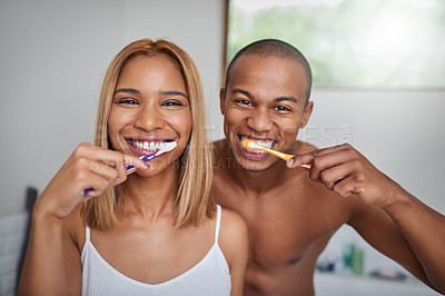 Buy stock photo Portrait of a young couple brushing their teeth together in the bathroom at home