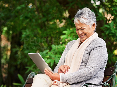 Buy stock photo Shot of a mature woman using a digital tablet outdoors