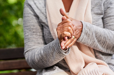 Buy stock photo Closeup shot of an unrecognizable woman holding her hands together outdoors