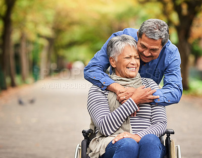 Buy stock photo Shot of a mature man pushing his wife in a wheelchair at the park