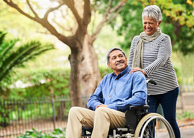 Buy stock photo Shot of a mature woman pushing her husband in a wheelchair at the park
