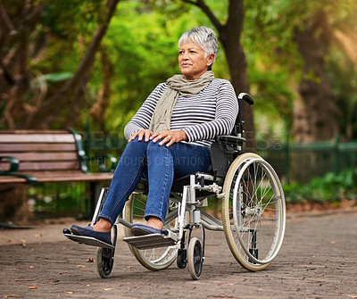 Buy stock photo Shot of a mature woman sitting in a wheelchair at the park