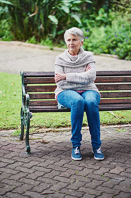 Buy stock photo Shot of a senior woman sitting on a park bench and frowning