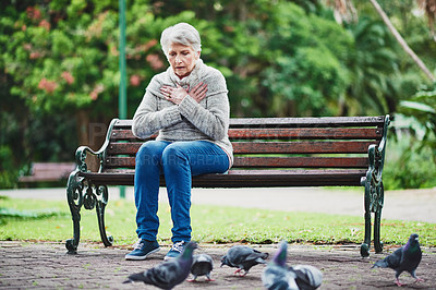 Buy stock photo Shot of a senior woman suffering from a heart attack in the park