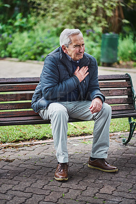 Buy stock photo Shot of a senior man suffering from a heart attack in the park