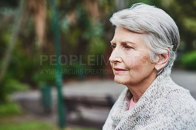 Buy stock photo Shot of a senior woman looking thoughtful in a park