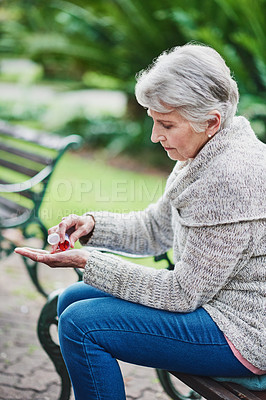 Buy stock photo Shot of a senior woman taking her medication in the park