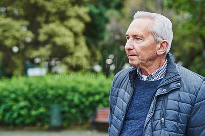 Buy stock photo Shot of a senior man looking thoughtful in a park