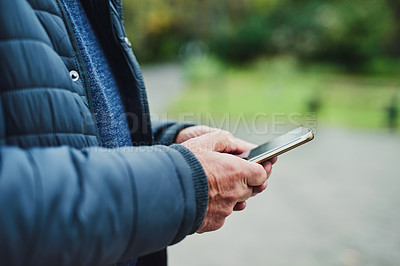 Buy stock photo Cropped shot of a senior man using a mobile phone in the park