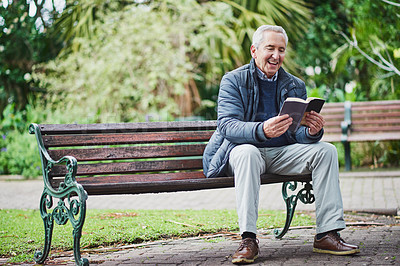 Buy stock photo Shot of a senior man reading a book and relaxing in the park