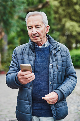 Buy stock photo Shot of a senior man using a mobile phone in the park