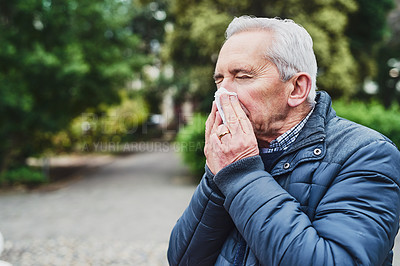Buy stock photo Shot of a senior man blowing his nose in the park