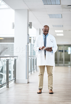 Buy stock photo Full length shot of a handsome mature male doctor using a tablet while standing in the hospital corridor