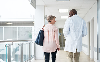 Buy stock photo Rearview shot of a handsome mature male doctor talking to a female patient in the hospital corridor