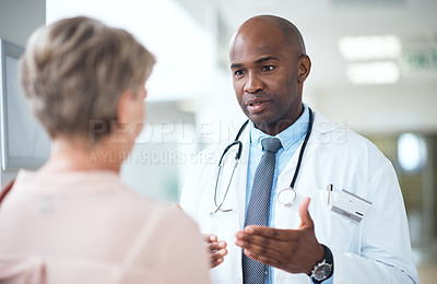 Buy stock photo Cropped shot of a handsome mature male doctor talking to a female patient in the hospital corridor
