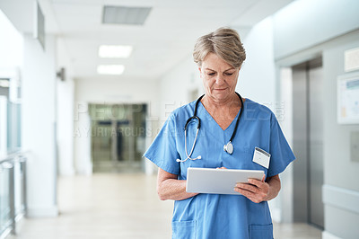 Buy stock photo Cropped shot of a mature female nurse using a tablet while standing in the hospital corridor