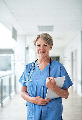 Buy stock photo Cropped portrait of a mature female nurse using a tablet while standing in the hospital corridor