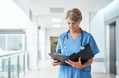 Buy stock photo Cropped shot of a mature female nurse reading through some medical reports while standing in the hospital corridor