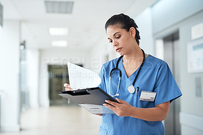 Buy stock photo Cropped shot of an attractive young female nurse reading through some medical reports while standing in the hospital corridor
