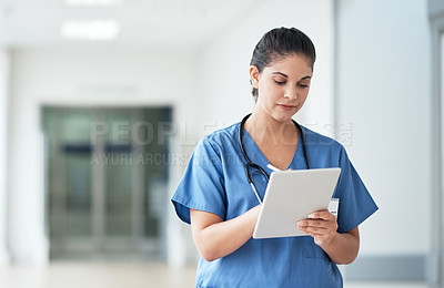 Buy stock photo Cropped shot of an attractive young female nurse using a tablet while standing in the hospital corridor