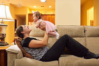 Buy stock photo Cropped shot of a mother picking up her adorable little baby daughter on the couch in the living room at home