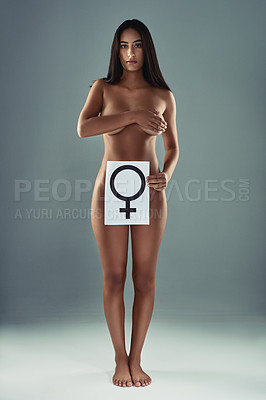 Buy stock photo Studio shot of an attractive young woman posing and holding a poster with the female symbol on it against a grey background