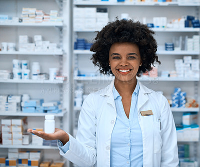 Buy stock photo Shot of a young pharmacist showing a bottle of pills at a chemist