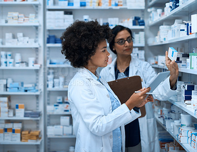 Buy stock photo Shot of two young women doing inventory in a pharmacy with a digital tablet