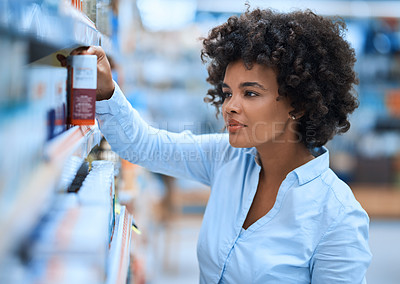 Buy stock photo Shot of a young woman browsing the shelves of a pharmacy